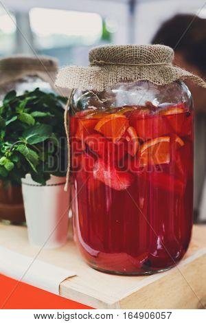 Closeup of lemonades in glass jars at restaurant background. Refreshing drinks in craft containers with sack on bar counter