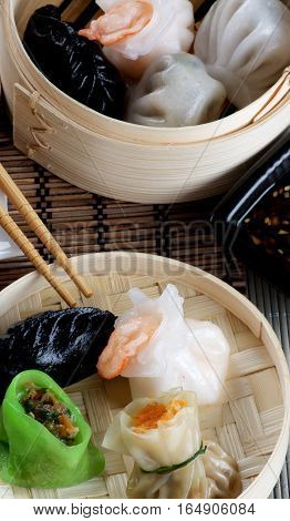 Arrangement of Various Dim Sum in Two Bamboo Steamed Bowls Black Chili Sauce and Chopsticks Cross Section on Straw Mat background