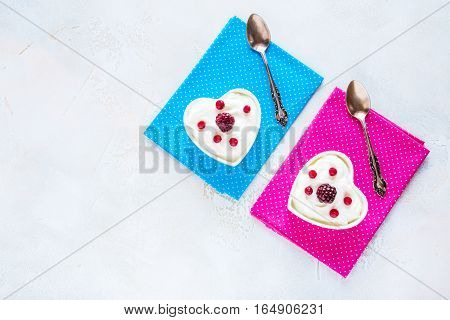 Valentine day decoration breakfast yogurt with berries for two in white heart-shaped bowls on the table. Top view flat lay.