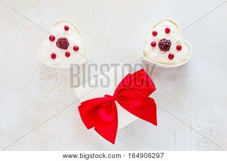 Valentine day decoration breakfast yogurt with berries for two in white heart-shaped bowls and gift box on the table. Top view flat lay.