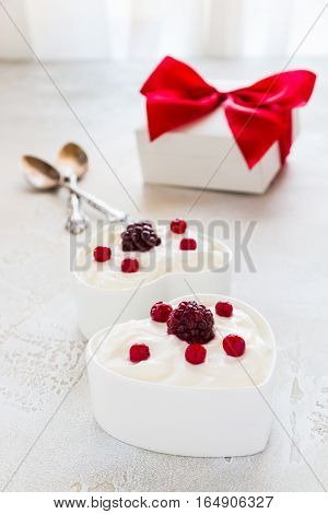 Valentine day decoration breakfast yogurt with berries for two in white heart-shaped bowls on the table.