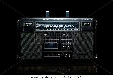 Vintage boom box on black background. Radio cassette