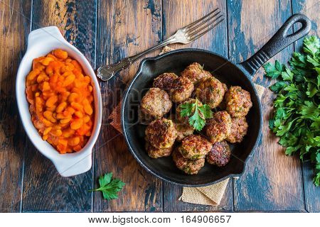 Homemade roasted beef meatballs in cast-iron skillet and beans baked in tomato sauce in baking dish on wooden table in kitchen fresh parsley vintage fork top view.
