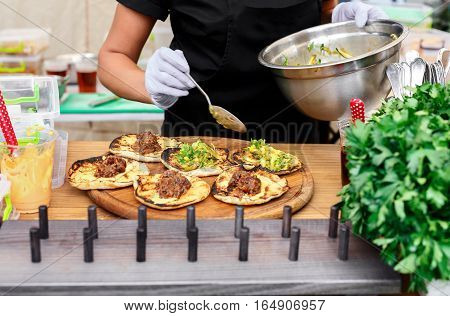 Female street vendor hands making meat and vegetables taco outdoors. Mexican cuisine snacks, cooking fast food for commercial kitchen.