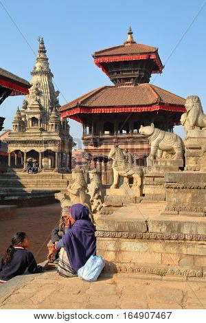 BHAKTAPUR, NEPAL - DECEMBER 29, 2014: Durbar Square with Nepalese women enjoying the sun