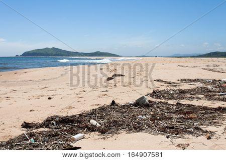 Various garbage on the sandy seashore thrown ocean waves. Yellow sand and blue sky. Wide angle.