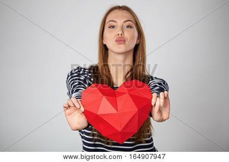 Beautiful woman giving outstretching red polygonal paper heart shape sending a kiss. Shallow depth of focus, focus on heart shape.