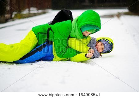 Two boys in bright winter overalls play on snow. It is snowing. Boys like to roll on a snow. They joyfully laugh.