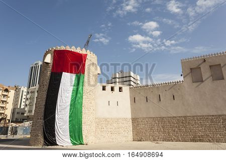 Historic fort decorated with UAE national flag in the city of Sharjah United Arab Emirates