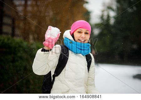 Charming young woman holds a snowball in hand. She is ready to throw him into someone. Woman is dressed in a bright cap a scarf and gloves. It is snowing. Woman smiles.