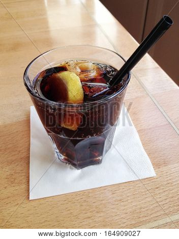 glass of cola with lemon slice and ice cubes