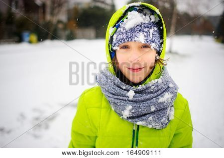 Portrait of the schoolboy walking in winter day. The boy is dressed in a bright jacket and a knitted cap and a scarf. His face and clothes are closed up with snow. The child happily smiles.