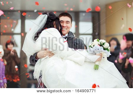 The groom brings the bride in his arms, the crowd throws petals and rice.