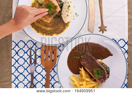A hand decorating nice dish of salmon steak and beef served with mashed potato,lemon, saute spinach and sauce on background with wooden utensils.
