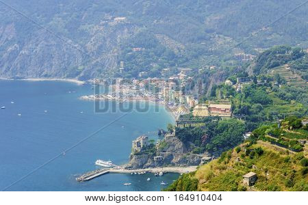 Aerial view of Monterosso Al Mare village La Spezia province Liguria northern Italy. Panoramic view of the sandy colorful beach gulf and the mountain hills. Part of the Cinque Terre National Park and a UNESCO World Heritage Site.