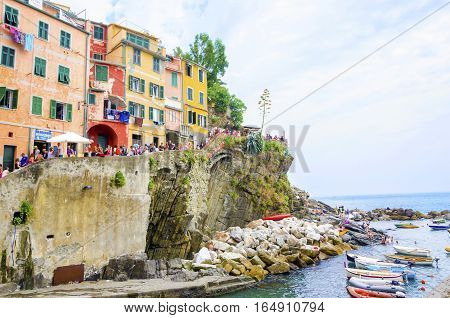 Riomaggiore village La Spezia province Liguria northern Italy. View of the colourful houses on steep hills sea rocks beach laundry on balconies boats and tourists. Part of the Cinque Terre National Park and a UNESCO World Heritage Site.