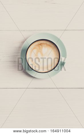 Cappuccino with frothy foam, blue coffee cup top view closeup on white wood background. Cafe and bar, barista art concept. Filtered, vertical