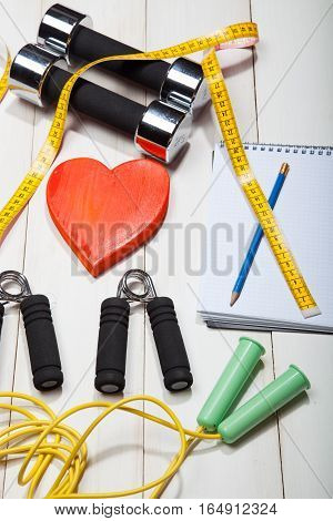 Heart, dumbbells, skipping rope and the expander on a white wooden background