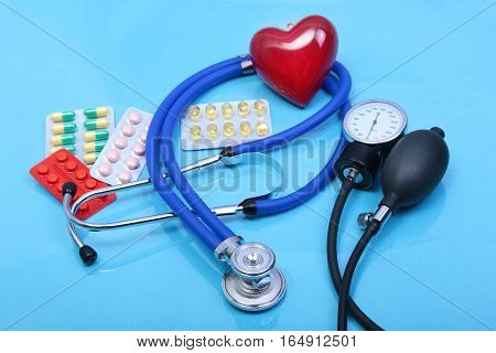 Red heart and a stethoscope on blue background.