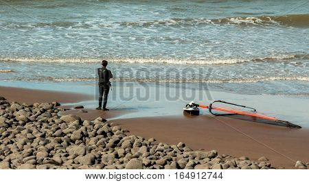 Surfer take a rest after surf in front of the water in Minehead Somerset UK