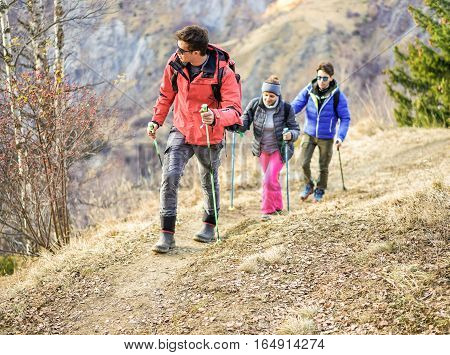 Tour scout guide bringing young couple for trekking excursion - People hiking high mountain in france - Survivaltravel and adventure concept - Focus on left man face - Warm vivid filter