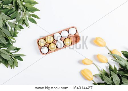 Easter Composition: A Tray With Colored Eggs And Tulips On White Background