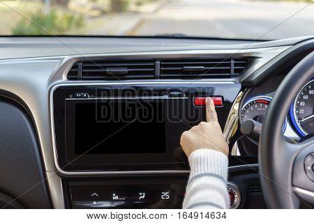 woman finger pressing emergency button on car dashboard