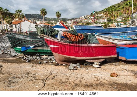 Camara de Lobos Madeira Portugal - December 10 2016: Fishing boats drawn up on beach and slipway at Camara de Lobos in Madeira Island Portugal.