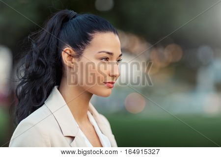 Woman smiling - side view portrait of happy lovely and beautiful mixed race asian caucasian young businesswoman in casual clothes outdoor in the city park