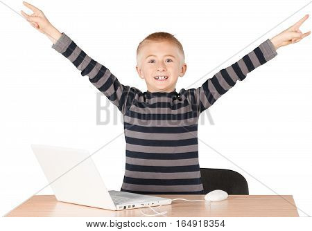 Young boy celebrating with open arms over laptop on desk