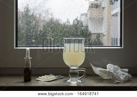 common cold or flu remedy. hot lemonade, nasal spray, pills, and tissues on window sill.