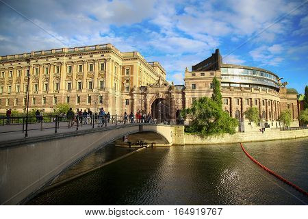 STOCKHOLM SWEDEN - AUGUST 19 2016: People walk and visit on Norrbro bridge and view on parliament building (the former Riksbank) located on Helgeandsholmen in Stockholm Sweden on August 19 2016.
