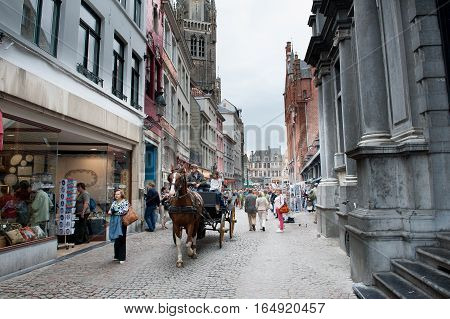 Bruges Belgium - August 7 2012. City street with people and typical horse cart walking around in daytime