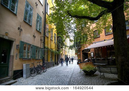 STOCKHOLM SWEDEN - AUGUST 19 2016: View of narrow street and colorful buildings in Gamla Stan people walk and visit on Gamla Stan old town in central Stockholm Sweden on August 19 2016.