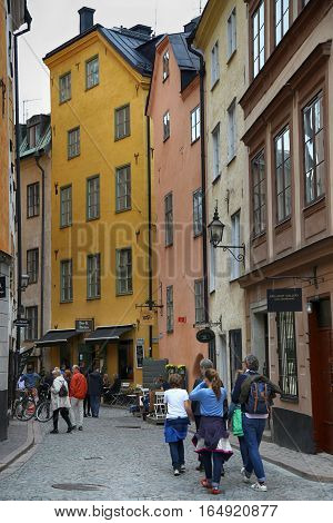 STOCKHOLM SWEDEN - AUGUST 19 2016: View of narrow street and colorful buildings in Gamla Stan tourists walk and visit on Gamla Stan old town in central Stockholm Sweden on August 19 2016.