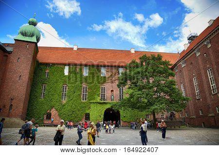 STOCKHOLM SWEDEN - AUGUST 19 2016: Tourists walk and visit Stockholm City Hall courtyard ( Stadshuset ) Ivy covered walls at City Hall in Stockholm Sweden on August 19 2016.