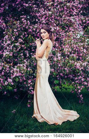 Portrait of young beautiful woman posing among spring blossom trees. Professional make-up and hairstyle. Perfect skin. Long evening dress. Fashion photo. Natural beauty.