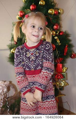 Portrait of cute young girl with pigtail posing in front of Christmas tree