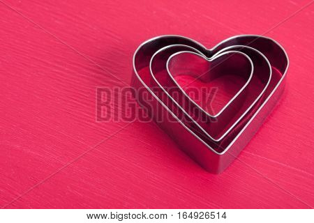 Valentine Background With Three Metal Hearts On Pink Wood.
