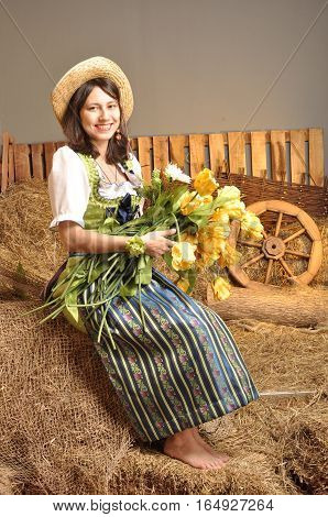 The girl in the dress hat with flowers in their hands in the hayloft