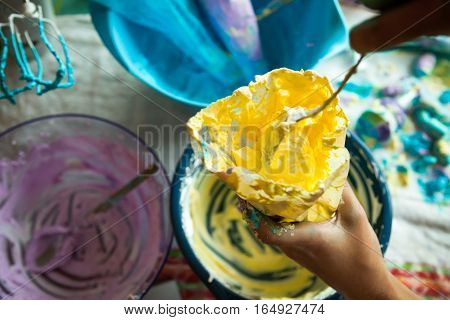 Close up of hand filling pastry bag with yellow cream