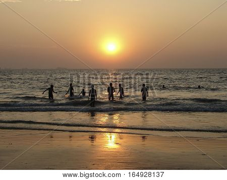 few people bathed in the ocean against the setting sun
