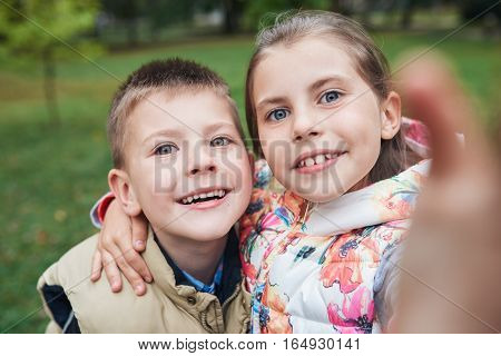 Portrait of a smiling little brother and sister taking a selfie while enjoying a day outside together in autumn