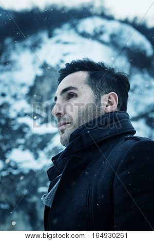 sideward portrait of attractive man in front of snowy mountain