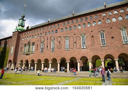 STOCKHOLM SWEDEN - AUGUST 19 2016: Tourists walk and visit Stockholm City Hall ( Stadshuset ) Venetian-style colonnade that divides the City Hall in Stockholm Sweden on August 19 2016.