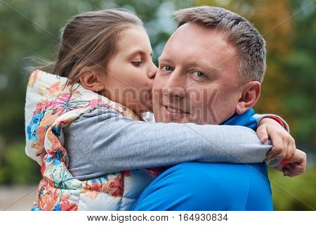 Portrait of a cute little girl hugging and kissing her smiling father while enjoying a day outside together in a park in the autumn