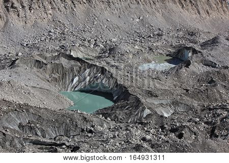 Big holes with glacier lakes on the Khumbu glacier. Everest National Park Nepal.