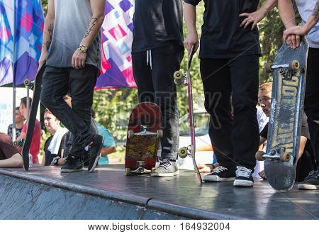 KAZAKHSTAN ALMATY - AUGUST 28, 2016: Urban extreme competition, where the city athletes compete in the disciplines: skateboard, roller skates, BMX. Bmx stunt performed at the top of a mini ramp on a skatepark.Winners team on the mountain top. Sport and ac