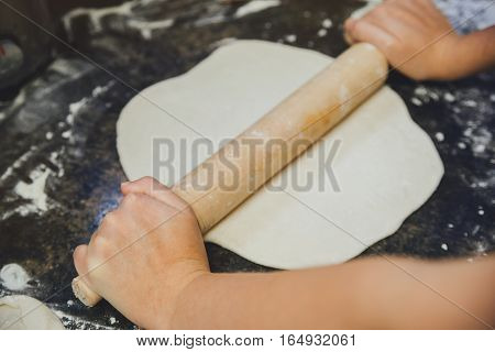 Cook rolls rolling pin yeast dough in the kitchen