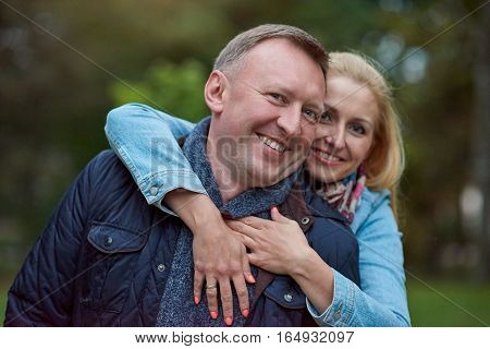 Portrait of a smiling mature woman hugging her husband from behind while standing together in a park in the autumn